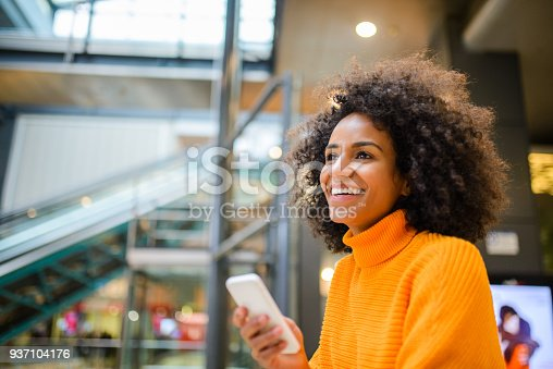 istock Smiling woman using mobile phone. 937104176