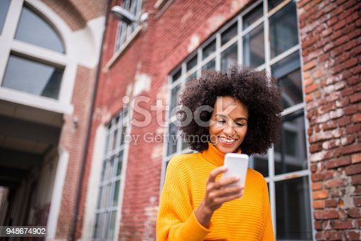 istock Smiling woman using mobile phone. 948674902