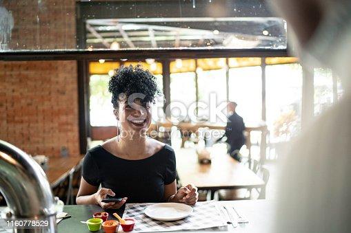 946192604 istock photo Smiling woman using phone at restaurant 1160778529