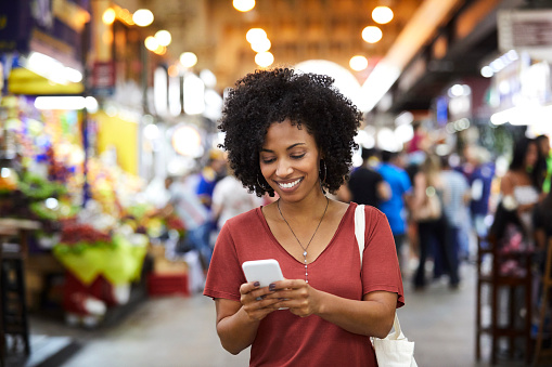 Smiling woman text messaging on smart phone. Happy female customer with curly hair is wearing casuals. She is shopping at supermarket.