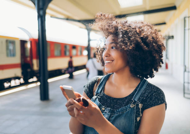 Smiling woman using smart phone on station Smiling woman using smart phone on station, wears casual clothes. subway platform stock pictures, royalty-free photos & images