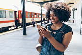Smiling woman using smart phone on station, wears casual clothes.
