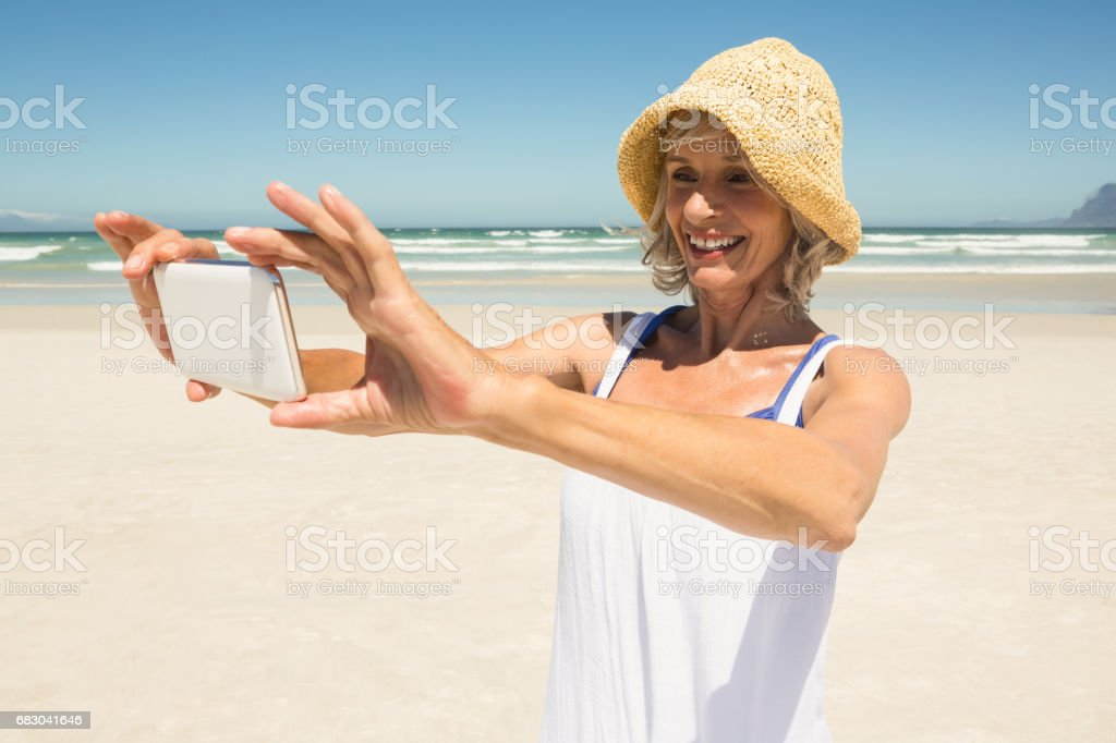 Smiling woman using smart phone while standing at beach royalty-free stock photo