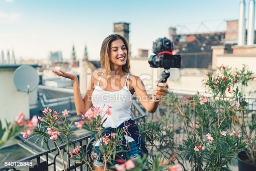 istock Smiling woman vlogging at rooftop terrace 840128348
