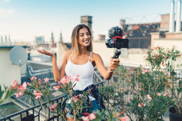 Smiling woman vlogging at rooftop terrace stock photo
