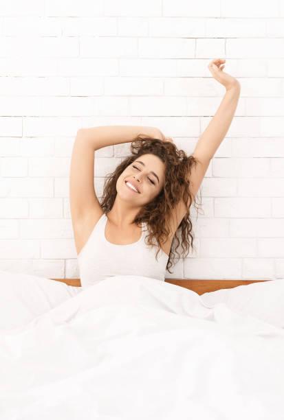 lächelnde frau wacht in ihrem bett auf - aufwachen stock-fotos und bilder