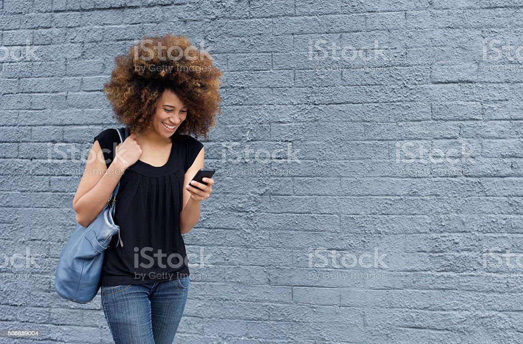 Smiling woman walking and looking at mobile phone stock photo