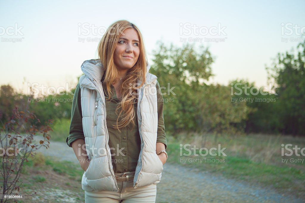 Smiling woman walking in forest stock photo