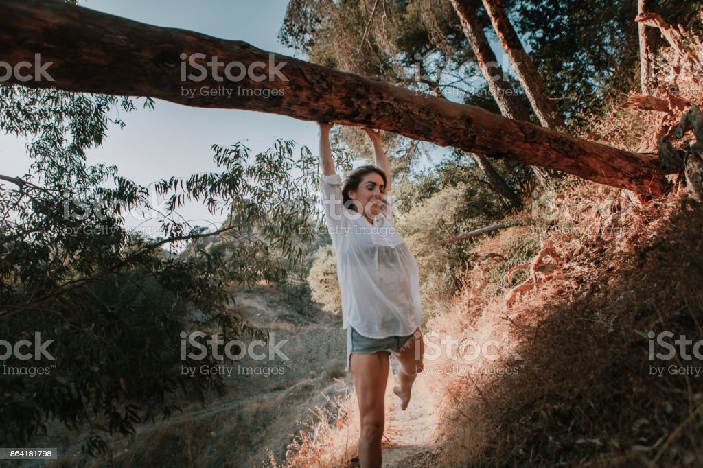 Smiling woman walking in nature and hanging from a fallen tree royalty-free stock photo