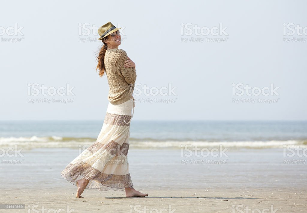 Smiling woman walking on the beach royalty-free stock photo