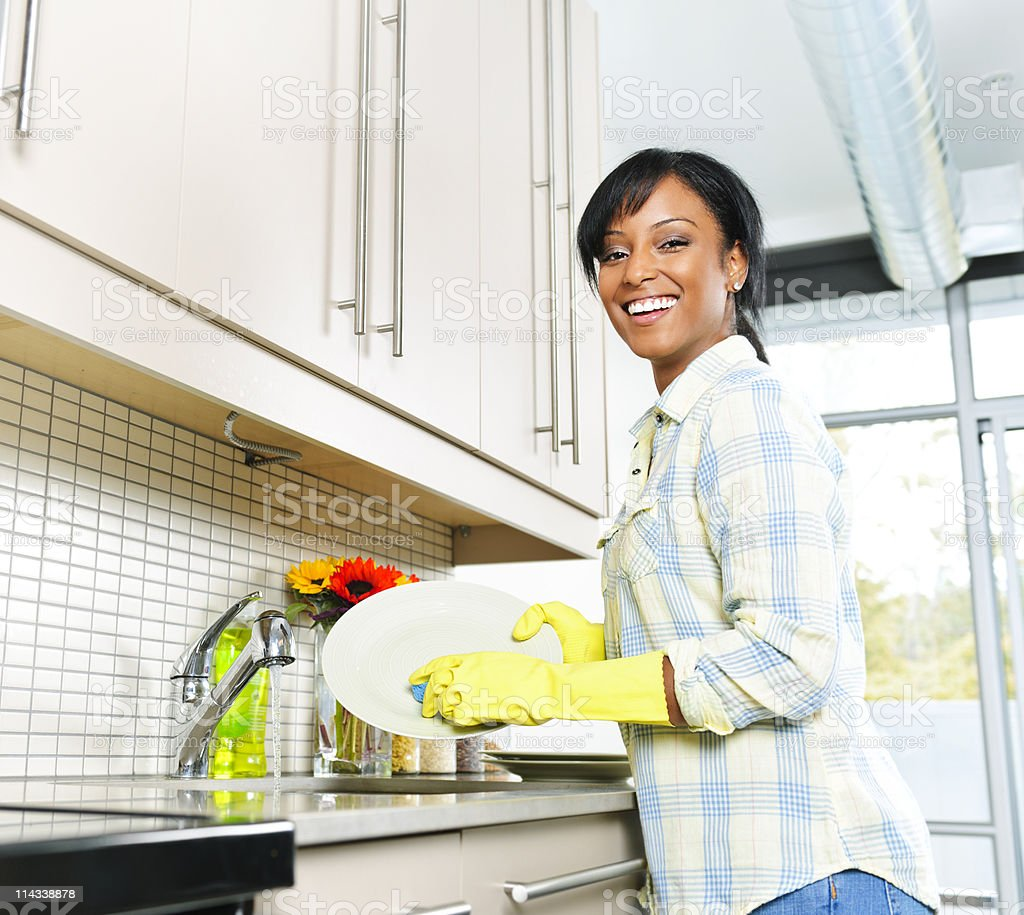 Smiling woman washing dishes in the kitchen stock photo
