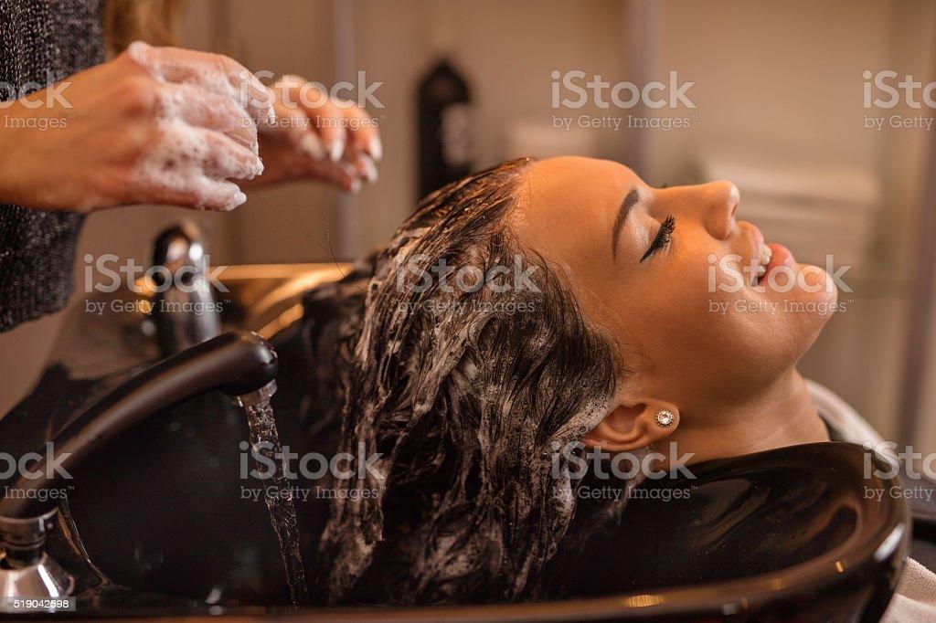 Smiling woman washing hair at hairdressers. stock photo