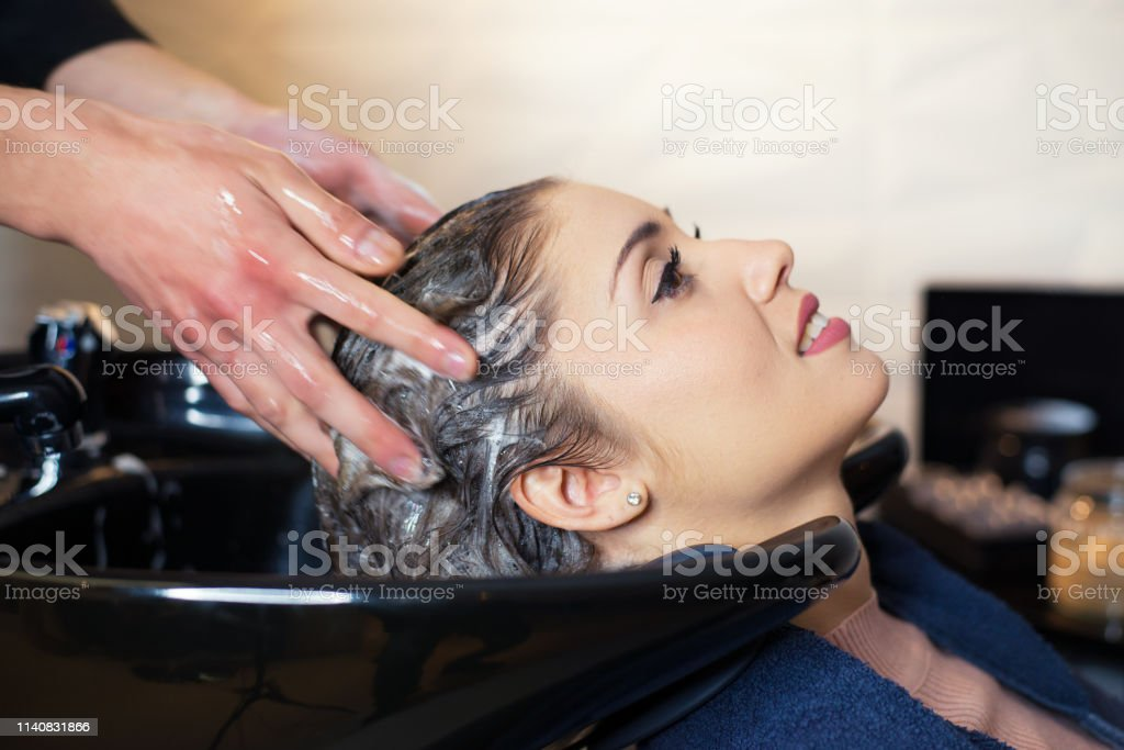 Young smiling woman washing long hair in the professional hair salon.