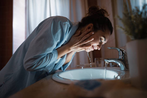 Smiling woman washing her face in the evening. Young smiling woman washing face in the bathroom. clean face stock pictures, royalty-free photos & images
