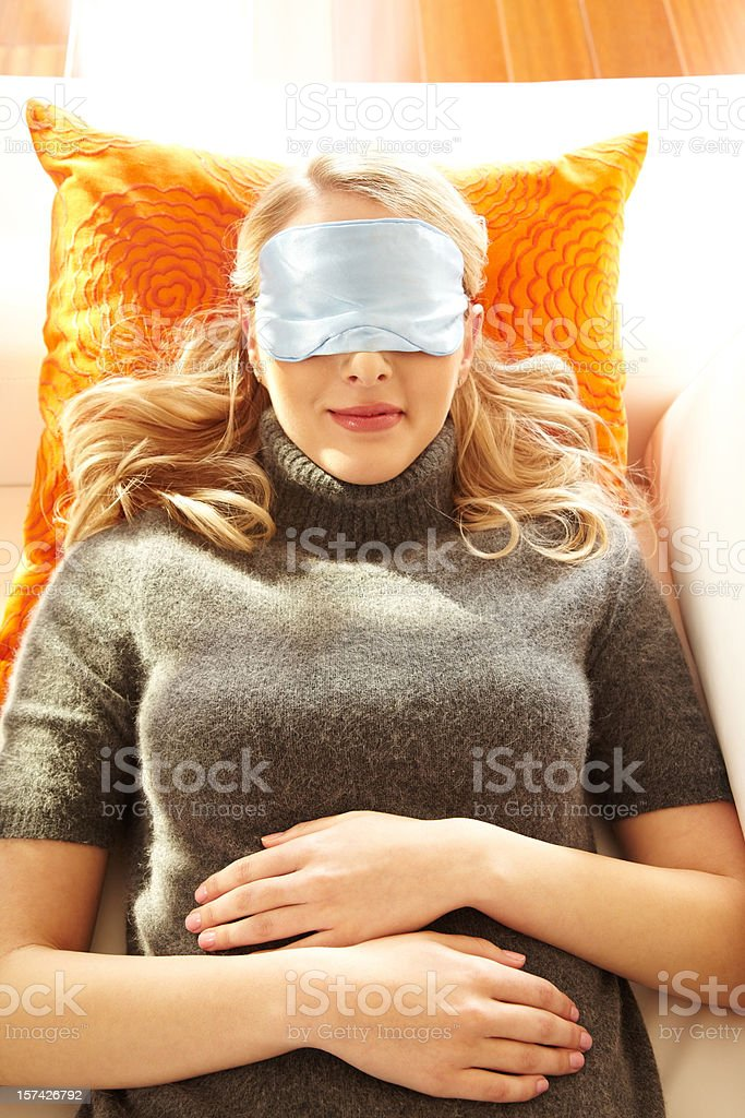 Beautiful young blond woman with an eye pillow resting on couch