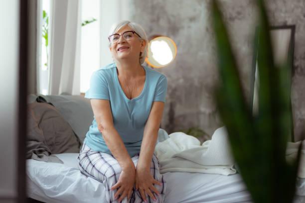 lächelnde frau, die brille und pajama auf dem bett sitzt - sexy granny stock-fotos und bilder