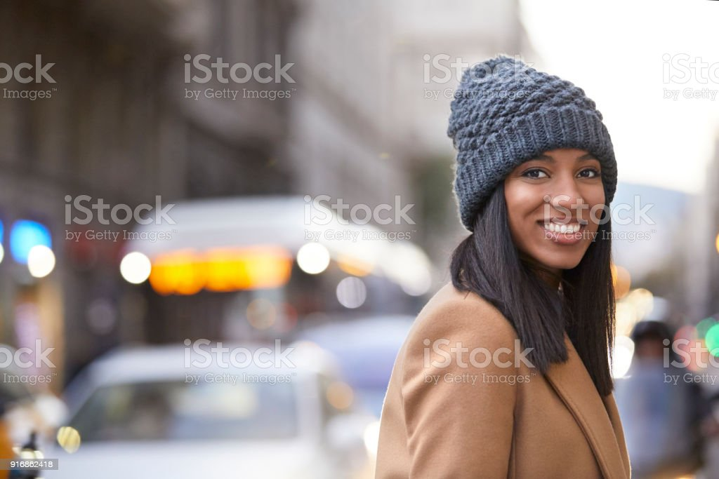 Smiling woman wearing knit hat on city street stock photo