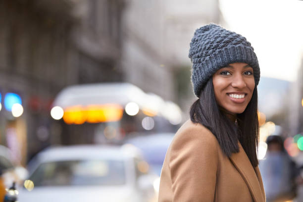Smiling woman wearing knit hat on city street Portrait of smiling young woman wearing knit hat. Beautiful female is standing on city street. Tourist is enjoying her vacation. straight hair stock pictures, royalty-free photos & images