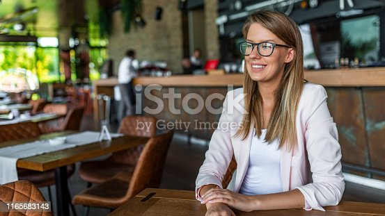 618976144istockphoto Smiling woman wearing spectacles. 1165683143