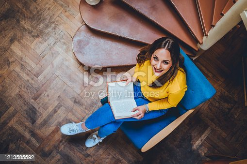 834814926 istock photo Smiling woman with a book 1213585592