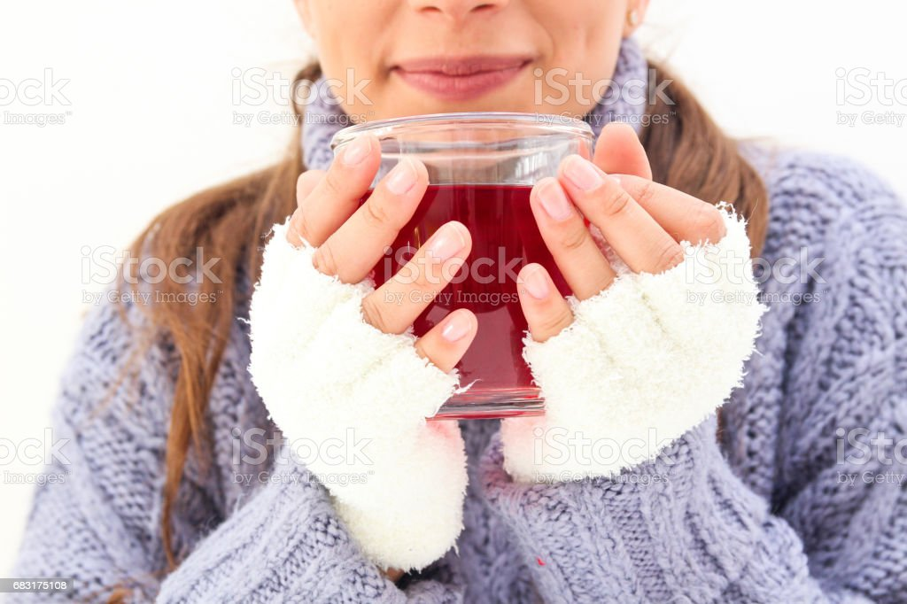 A smiling woman with a cup of red tea wears a purple sweater and white gloves 免版稅 stock photo