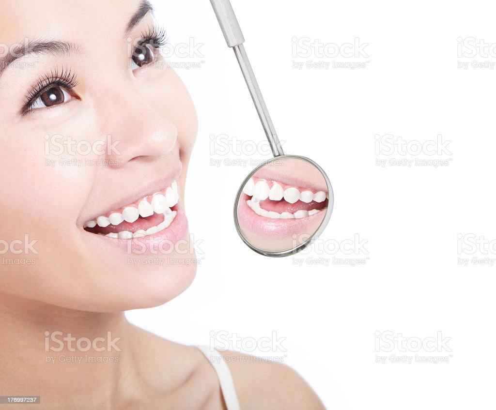 Smiling woman with a dentists mirror showing her teeth stock photo