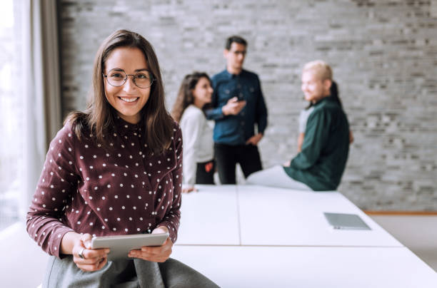 Smiling woman with a table t in office Portrait of a young smiling businesswoman with a tablet office jobs stock pictures, royalty-free photos & images