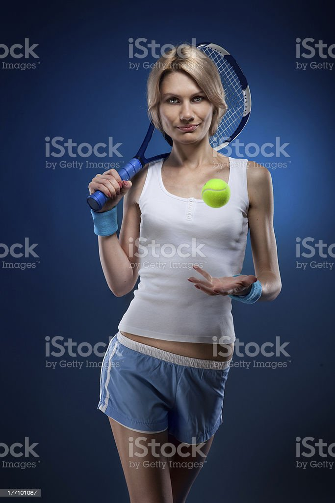 smiling woman with a tennis ball and racquet on blue royalty-free stock photo