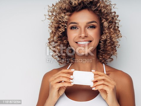Smiling woman with afro curls holding blank card