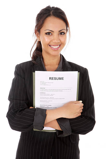 Smiling woman with arms crossed on resume documents stock photo