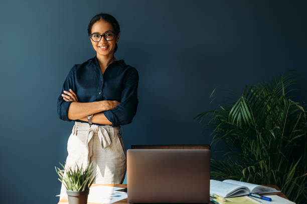 Smiling woman with arms crossed stands at her workplace in home office stock photo