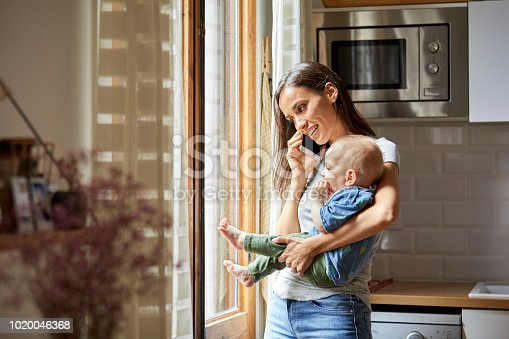 Smiling woman talking on mobile phone while carrying baby. Mother is holding son while using technology. They are in casuals at home.
