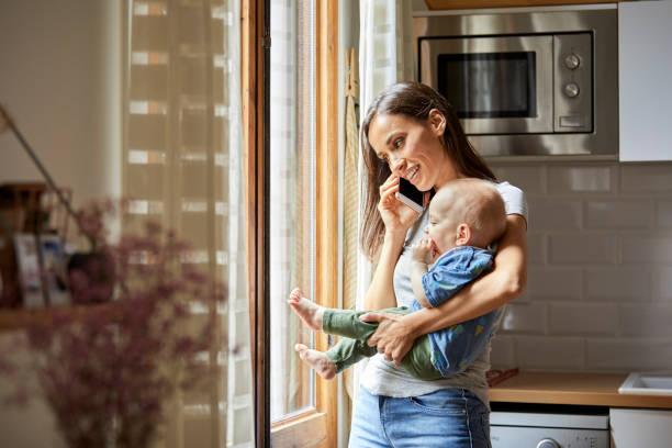 Lächelnde Frau mit Baby zu Hause telefonieren – Foto