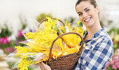 smiling woman with basket full of mimosa spring flowers, 8 March Women's Day concept
