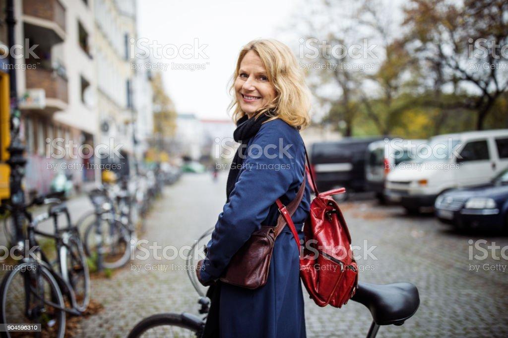 Lächelnde Frau mit dem Fahrrad in die Stadt im winter – Foto