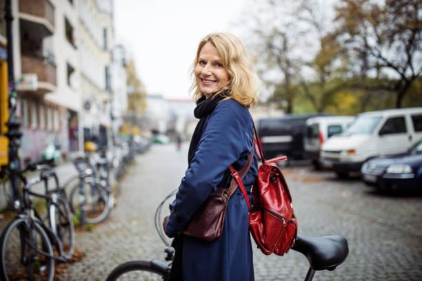 lächelnde frau mit dem fahrrad in die stadt im winter - deutsche frauen stock-fotos und bilder