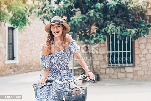 Smiling young woman riding a bike