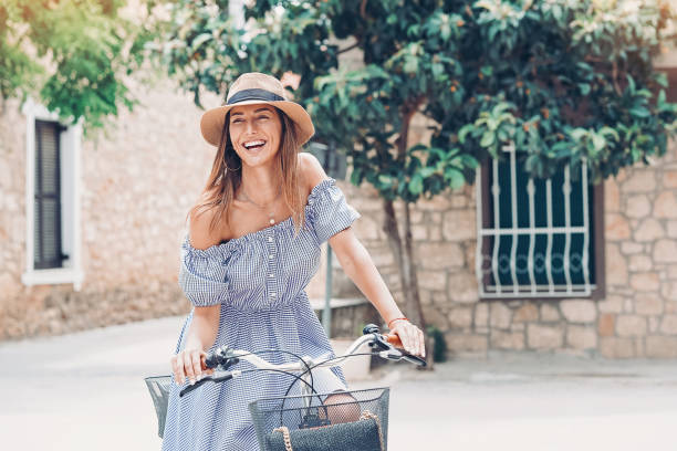 Smiling woman with bicycle on a town street stock photo