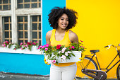 istock Smiling woman with bike carrying flowers in pot 867612610