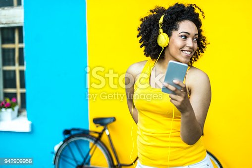 Smiling african woman with bike using smart phone in front of blue and yellow wall backgound.