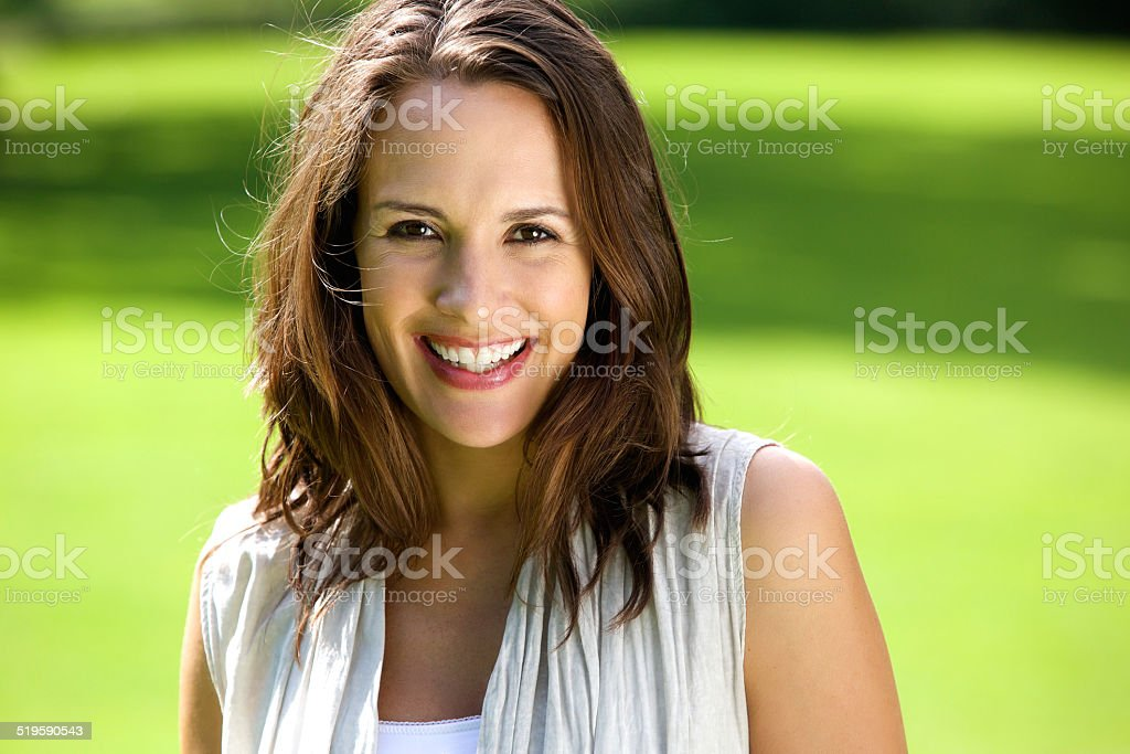 Smiling woman with brown hair posing outdoors stock photo