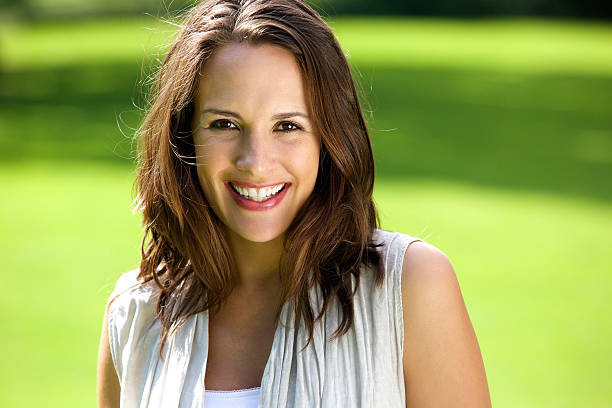 smiling woman with brown hair posing outdoors - medium length hair stock photos and pictures