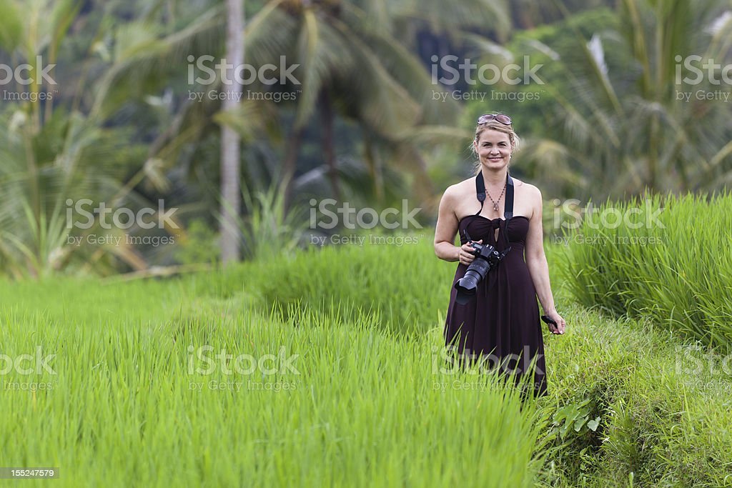 Smiling Woman with Camera in Bali Rice Field stock photo
