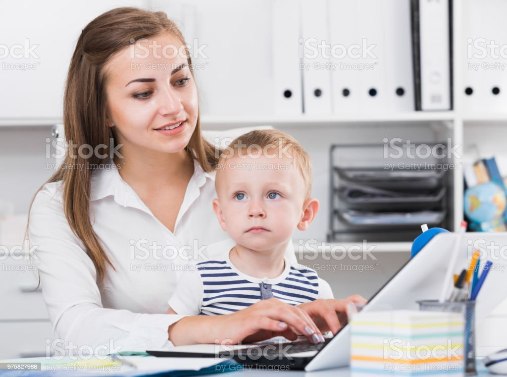 Lächelnde Frau mit Kind ist hinter Laptop produktiv arbeiten. - Lizenzfrei Alleinerzieherin Stock-Foto