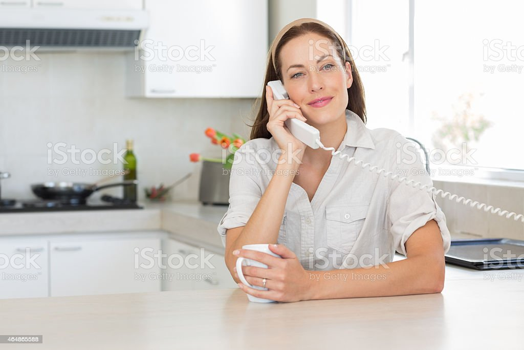 Smiling woman with coffee cup using landline phone in kitchen stock photo