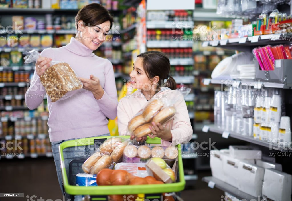 smiling woman with daughter choosing bread in supermarket stock photo