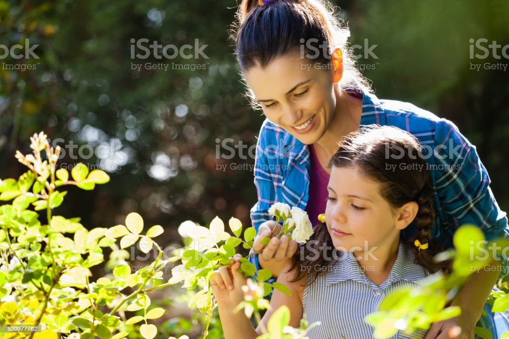 Smiling woman with daughter smelling white roses stock photo