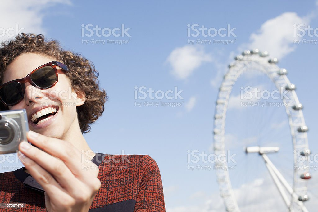 Smiling woman with digital camera in front of ferris wheel royalty-free stock photo