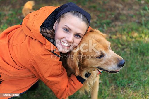 Smiling woman embracing a dog in park, looking at camera.