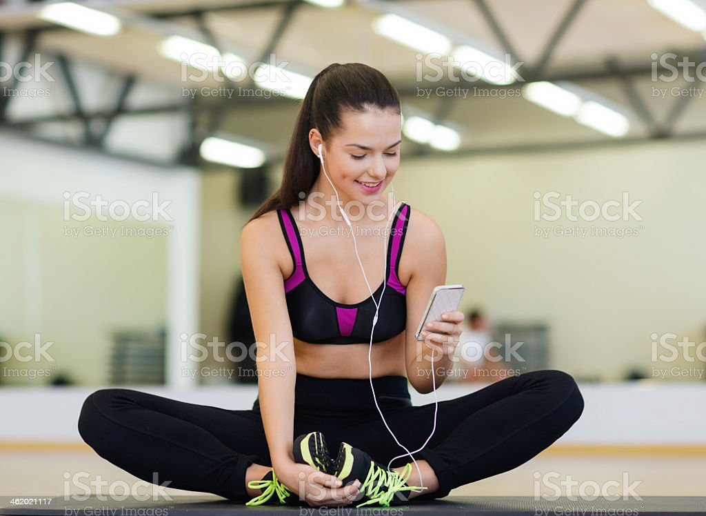 smiling woman with earphones and cellphone in gym stock photo